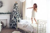 foto of preteen  - Preteen child girl wake up and jumping on her bed near decorated Christmas tree in beautiful hotel room in the holiday morning - JPG
