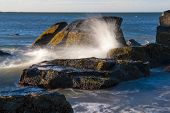 stock photo of dartmouth  - Water from breaking wave sheets off rock - JPG
