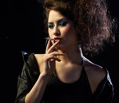 stock photo of hooker  - portrait of girl dressed like hooker smoking on black - JPG
