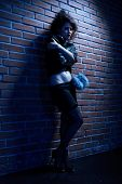 image of hooker  - portrait of girl dressed like hooker posing near brick wall - JPG