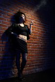 stock photo of pimp  - portrait of girl dressed like hooker posing near brick wall - JPG
