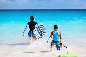 picture of boogie board  - Father and son running towards ocean with boogie boards having fun on beach vacation - JPG