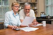 foto of receipt  - Senior couple working out their bills at home in the kitchen - JPG