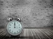 stock photo of count down  - Alarm clock counting down to twelve against grey room - JPG