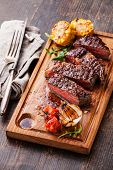 picture of ribeye steak  - Sliced medium rare grilled Beef steak Ribeye with corn and cherry tomatoes on cutting board on wooden background - JPG