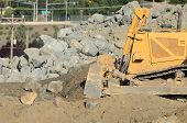 stock photo of bulldozer  - Tracked bulldozer working a rock pile at a large construction site removing a hill during an airport runway expansion project - JPG