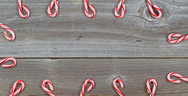 pic of candy cane border  - Top view close up of candy canes forming border on rustic wooden boards - JPG