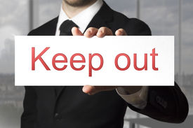 pic of underage  - businessman in black suit holding sign keep out - JPG