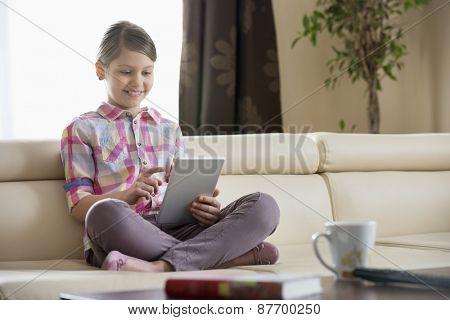 Smiling girl using digital tablet on sofa at home