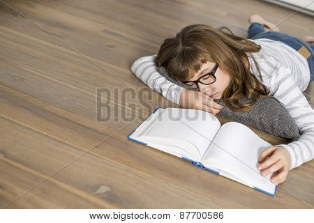 High angle view of teenage girl sleeping while studying on floor