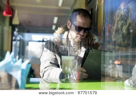Russian man with beard sitting inside a cafe in glasses