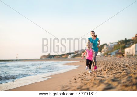 Healthy Mother And Baby Girl Running On Beach In The Evening