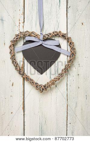 Geflochtesnes Herz Mit Tafel Vor Weißen Holzbrettern