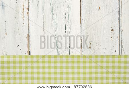 Green Checkered Tablecloth On A White Wooden Background