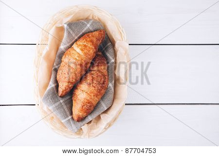 croissants in a basket on wooden table