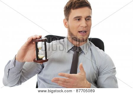 Talking businessman holding hourglass in the office.