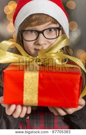 Close-up portrait of cute girl holding wrapped Christmas present