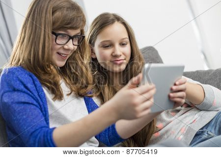 Sisters using digital tablet together at home
