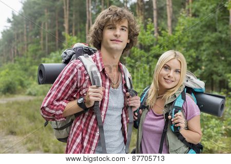Portrait of confident young hiking couple in forest