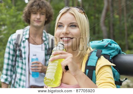 Hiking couple with energy drinks in forest