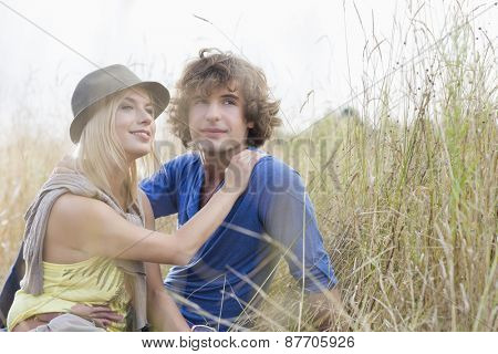 Loving young couple looking away while sitting in field