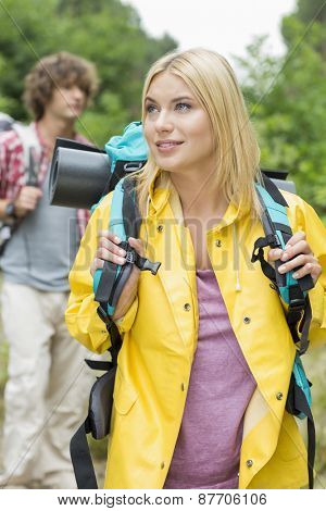 Female backpacker with man standing in background at forest