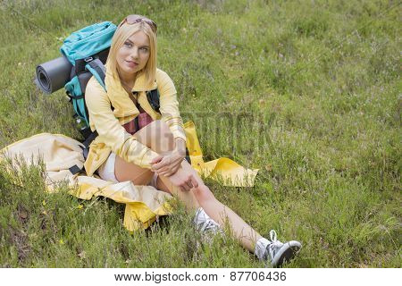 Full length of thoughtful female hiker sitting on grass