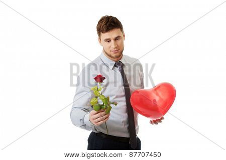 Young happy man with a red rose and heart balloon.