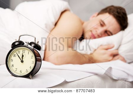 Man lying on the bed with alarm clock.