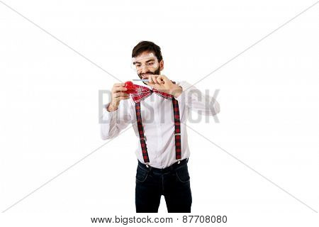 Funny man wearing suspenders cutting heart model with scalpel..
