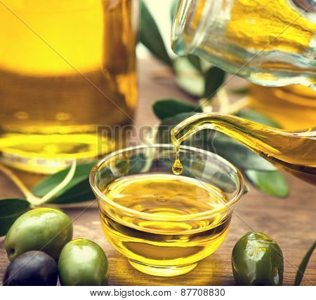 Olive Oil. Bottle pouring Virgin Olive Oil in a bowl close up. Olives and Healthy Olive oil being poured from glass bottle. Diet. Dieting concept. Healthy eating