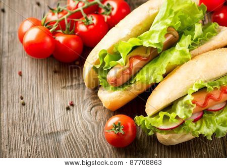Hot dog. Grilled hot dogs with mustard and ketchup on a picnic wooden table. Sandwich