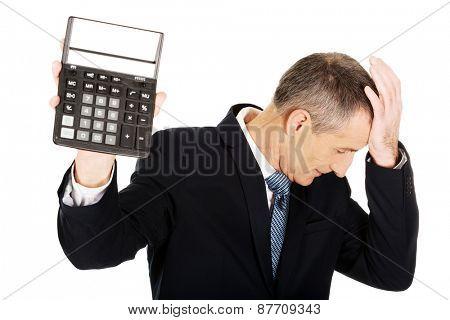 Depressed mature businessman holding a calculator.
