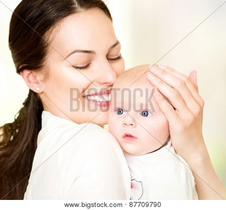 Mother and her Newborn Baby together. Happy Mother and Baby kissing and hugging. Beautiful Family. Maternity concept. Parenthood. Motherhood