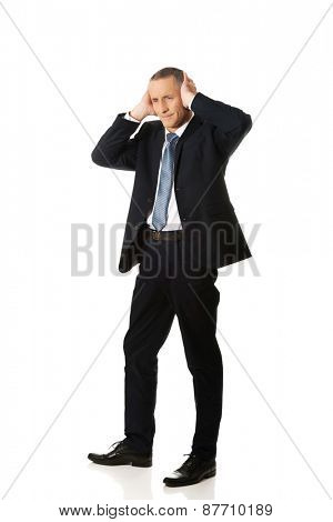 Tired mature businessman covering ears with hands