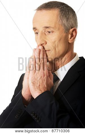 Portrait of hopeful businessman with clenched hands.