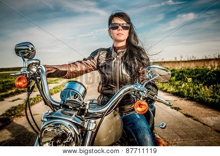 Biker girl in a leather jacket on a motorcycle looking at the sunset.