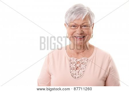 Closeup portrait of happy elderly granny, smiling, looking at camera.