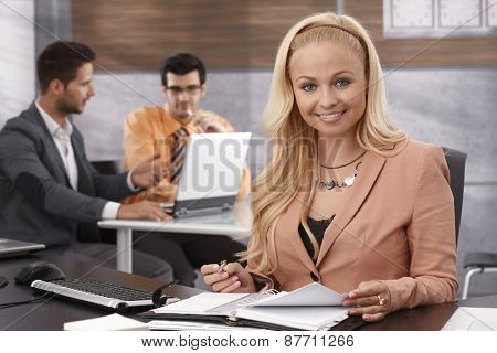 Portrait of beautiful young businesswoman sitting at desk in office, working, smiling, looking at camera.