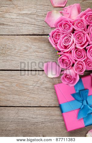 Valentines day background with gift box full of pink roses over wooden table. Top view with copy space