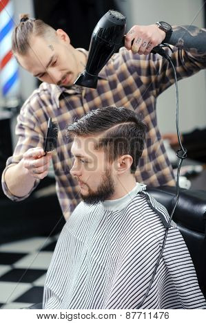 Hairdresser dries hair of a male client