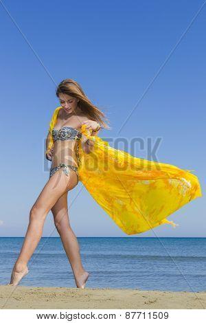 Young woman in bikini holding a yellow sarong on windy beach