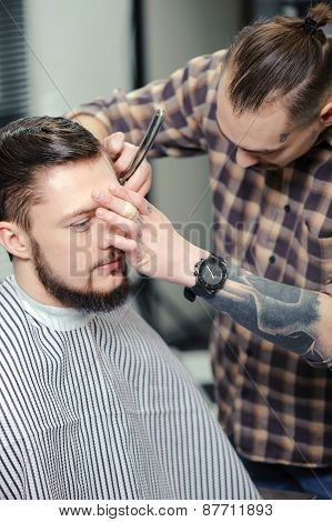 Barber shaves a client with razor