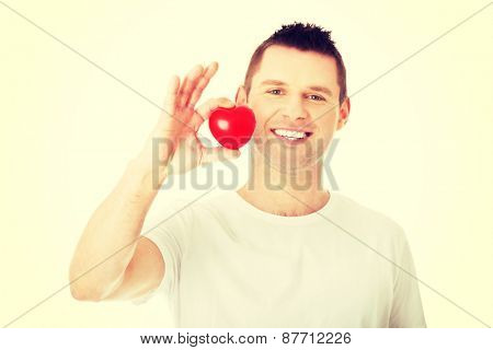 Young man holding a red heart shaped toy