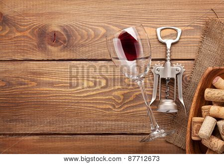 Red wine glass, corkscrew and bowl with corks over rustic wooden table background. Top view with copy space