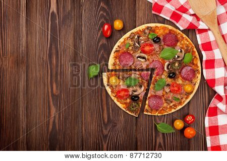 Italian pizza with pepperoni on wooden table. Top view with copy space