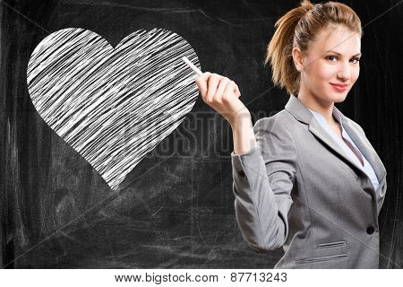 Portrait of a woman in front of an heart drawn on a blackboard