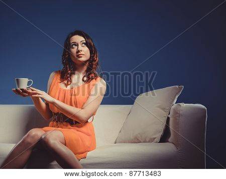 Girl Holds Tea Cup Sitting On Sofa