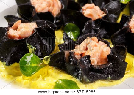 Open black ravioli with salmon