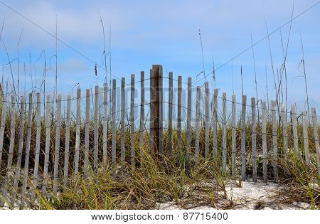 Weathered beach fence in sand dunes